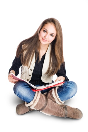 Portrait of a beautiful cute young student girl sitting and reading. photo