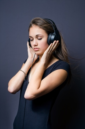Portrait of a tranquil young brunette immersed in music. photo
