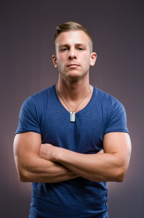 The bouncer, portrait of tough looking muscular young man, arms folded. photo