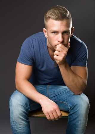dark blond: Thinking hard, portrait of a handsome young sitting and thinking.