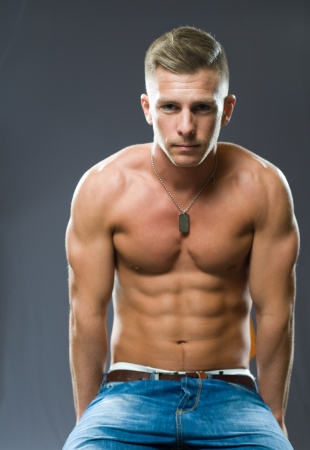 shirtless man: Portrait of a very fit, ripped young man flexing muscles. Stock Photo