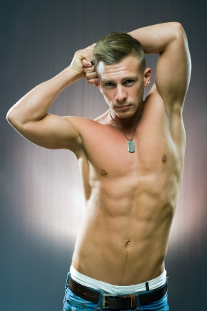 very fit handsome young man showing off muscles. photo