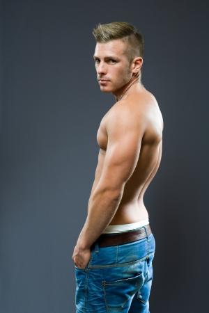 hombres musculosos: Atractivo joven rubio mirando hacia atr�s por encima del hombro.