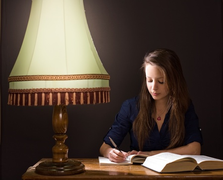Moody portrait of pretty young student girl studying at home late night. photo