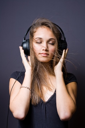Portrait of a gorgeous young brunette listening to music in headphones photo