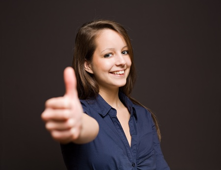 smirk: Gorgeous happy young brunette woman showing thumbs up.