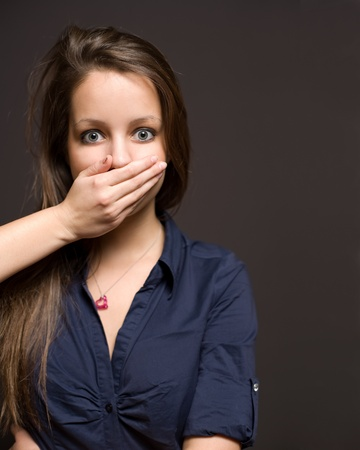 silenced: Wide eyed scared looking young brunette woman being silenced.
