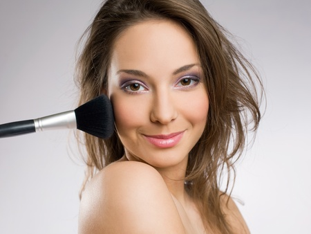 Beautiful young brunette woman getting her makeup done with brush. photo