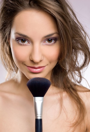 Portrait of a gorgeous young brunette with beautiful makeup and brush. photo