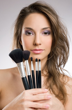 Portrait of a beautiful tanned young brunette holding assortment of brushes. photo
