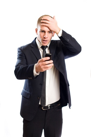 Portrait of a handsome young businessman string at his mobile phone with surpirsed expression  photo