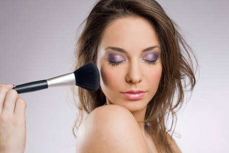 Gorgeous young brunette woman getting an elegant makeup. photo