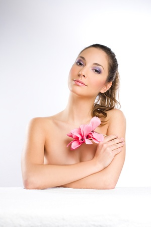 lilac background: Portrait of a gorgeous young brunette spa girl with pink flowers  Stock Photo