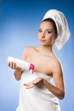 bathing: Beautiful young brunette woman after spa applying moisturizer