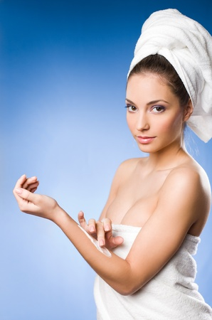 woman in towel: Portrait of a gorgeous brunette spa  woman using moisturizer on blue background