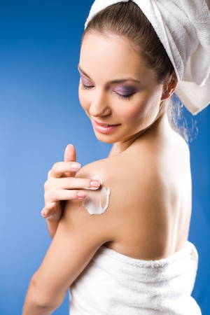 sexy shower: Portrait of a gorgeous brunette spa  woman using moisturizer on blue background