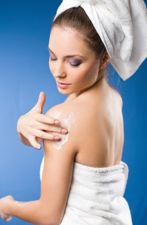 Beautiful young brunette woman after spa applying moisturizer Stock Photo - 12622132