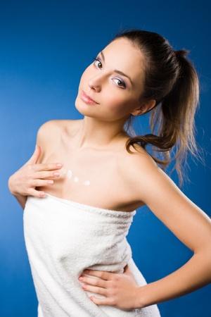 mujer bañandose: Retrato de una mujer joven y bonita con leche para el cuerpo sobre fondo azul