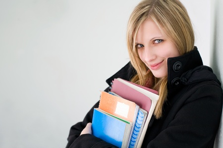 Portrait of a beautiful young blond student girl outdoors, dressed for cold weather. photo