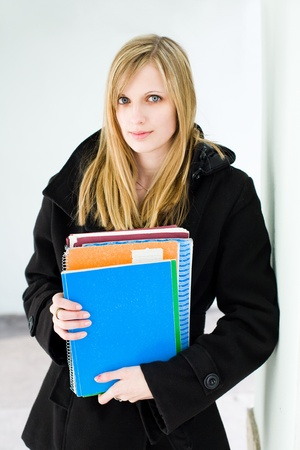 book jacket: Portrait of an attractive blond student woman holding colorful exercise books, dressed for cold weather.