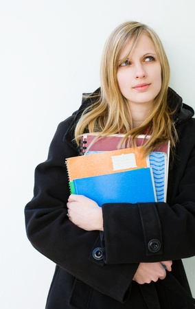 Portrait of a cute young student girl outdoors in warm clothing. photo