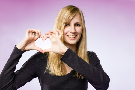 Portrait of a blond beauty on pink background showing heart sign. photo