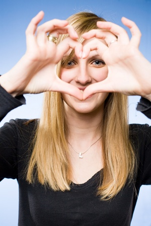 Portrait of beautiful young blond woman showing heart sign in front of her face. photo