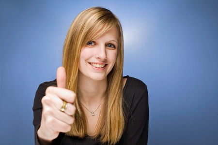 thumbs up woman: Portrait of a young blond beauty showing thumbs up on blue background. Stock Photo
