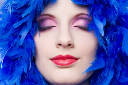 feather boa: Extreme colorful  closeup makeup cosmetics shot with young woman.