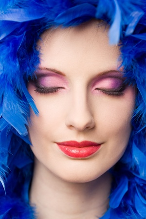 Very colorful  makeup cosmetics shot with young woman and blue feather boa. photo