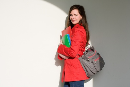 Portrait of a friendly very colorful young student girl holding exercise books. Imagens