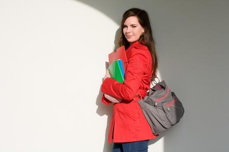 Ritratto di una ragazza molto amichevole colorato giovane studente in possesso quaderni. Archivio Fotografico