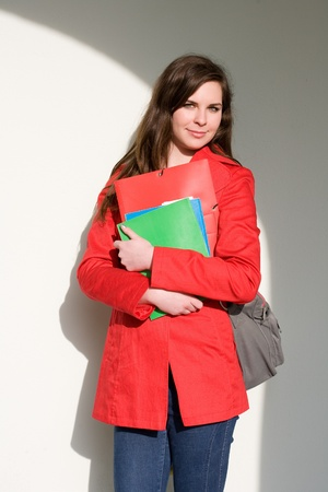 Portrait of a confident friendly young student woman in bright red coat. photo