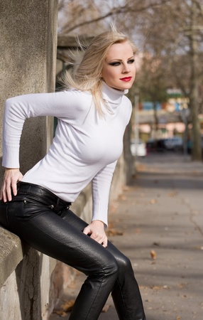 turtleneck: Attractive slender young blond beauty outdoors in white turtleneck sweater