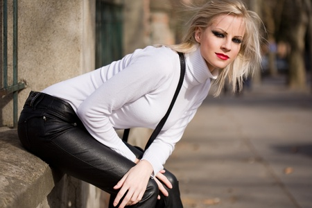 Attractive slender young blond beauty outdoors in white turtleneck sweater  photo
