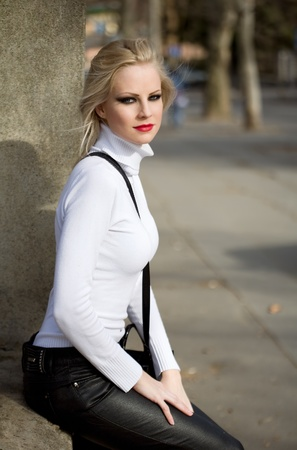 fashion portrait: Beautiful young blond fashion model posing on the street early spring