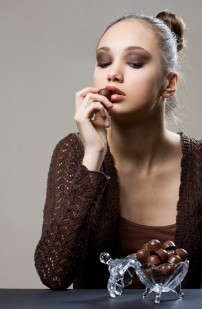 Chocolate dreams, artistic portrait of brunette eating bonbons  photo
