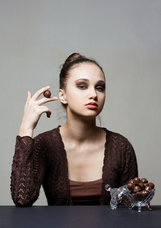 Dark chocolate beauty, portrait of a beautiful brunette with bonbons  photo