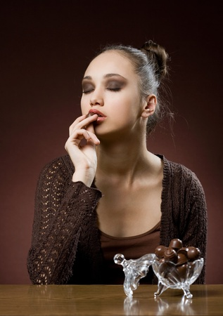 Chocolate dreams, artistic portrait of brunette eating bonbons Stock Photo - 13086074