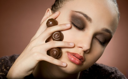 pralines: Gorgeous young brunette in dark makeup with chocolate  Stock Photo