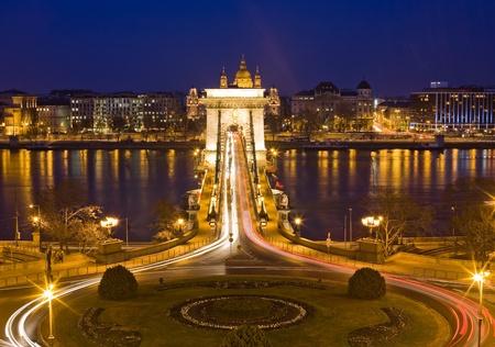 szechenyi: El famoso puente hist�rico de Szechenyi en Budapest en el tr�fico por la noche. Foto de archivo