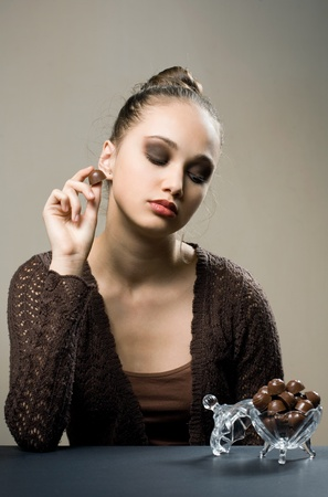 Chocolate addiction, moody portrait of gorgeous brunette with chocolate pralines  photo