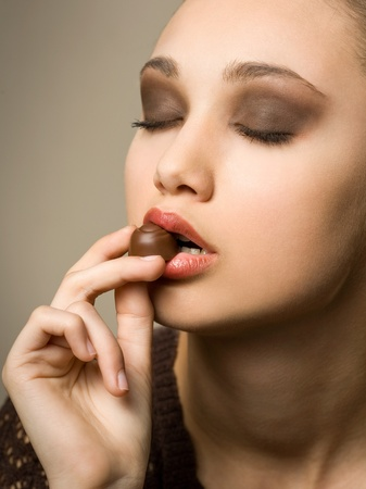 Chocolate cravings, beautiful young brunette with chocolate bonbons  photo