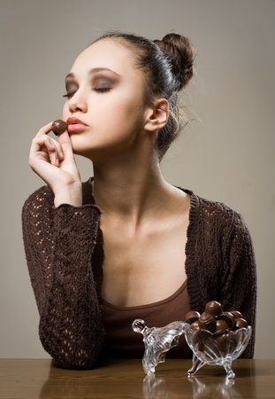Chocolate addiction, moody portrait of gorgeous brunette with chocolate pralines Stock Photo - 13166553