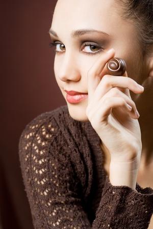 manjar: Adicción al chocolate, retrato de mal humor de la hermosa morena con bombones de chocolate Foto de archivo
