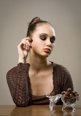 Luxury chocolate, stunning young brunette woman with bonbons  photo