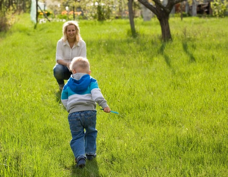 Fun in the garden, mother and son playing outdoors in nature. photo