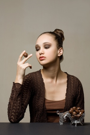 Striking beautiful brunette girl with tasty chocolate. photo
