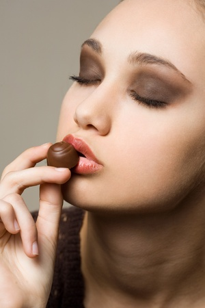 Gorgoeus young brunette loving tasty sweet chocolate. photo