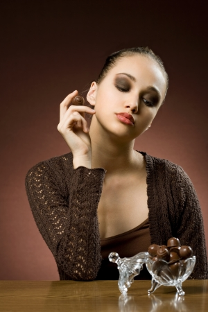pralines: Striking beautiful brunette girl with tasty chocolate.